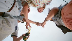 Under view of ginger man with moustache pouring champagne to his female friends. Graded stock video