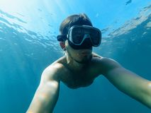 Under water the diver man in the mask is snorkeling. And taking a selfie of your face Royalty Free Stock Photography