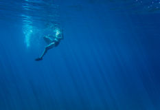 Under water. Man swims in blue sea. Photo taken under water with suns rays Stock Photo