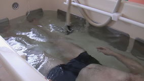 Under water massage. A man is lying in a bath with clear water and having  recreational massage on his leg by physical therapist in a rehabilitation center stock footage