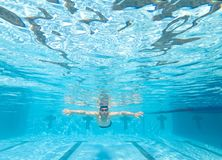 Underwater view of man in swimming pool. Under water view of man in swimming pool Royalty Free Stock Photography