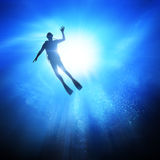 Under The Waves. Deep under the ocean, looking up towards a Diver Royalty Free Stock Image