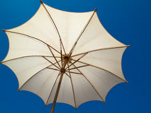 Under a white bamboo umbrella Royalty Free Stock Images