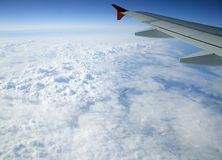 Under the wing of the aircraft. Flying above the clouds on a modern airliner Royalty Free Stock Images
