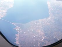 Under the wing of the plane. Panoramic view of the blue sky with clouds and the earth`s surface from a height. royalty free stock photography