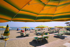 Under the yellow with green stripes umbrella on the sunny beach. In summer Stock Photography