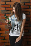 Underage drinking. Teenage girl holding a green bottle of beer against a brick wall Royalty Free Stock Photo