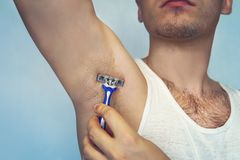 Underarm Haarabbau Männliche Enthaarung Junger attraktiver muskulöser Mann, der Rasiermesser verwendet, um Haar von seinem Körper stockbild