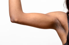 Underarm view of a muscular young woman. Underarm view of a muscular young African woman raising her arm and showing off her biceps isolated on white Stock Photo