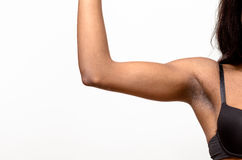 Underarm view of a muscular young woman. Underarm view of a muscular young African woman raising her arm and showing off her biceps isolated on white Royalty Free Stock Images