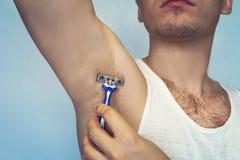 Underarm włosiany usunięcie Męska depilacja Młody atrakcyjny mięśniowy mężczyzna używa żyletkę usuwać włosy od jego ciała opieka  obraz stock