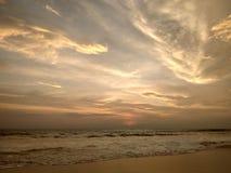 Underbar avkoppling på kusterna av det indiska havet som ser vågorna, färgade moln som reflekterar på den våta sanden Fotografering för Bildbyråer