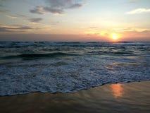 Underbar avkoppling på kusterna av det indiska havet som ser vågorna, färgade moln som reflekterar på den våta sanden Royaltyfria Foton