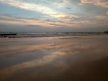 Underbar avkoppling på kusterna av det indiska havet som ser vågorna, färgade moln som reflekterar på den våta sanden Royaltyfri Foto