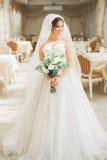 Underbar brud med en lyxig vit klänning och bukett royaltyfri foto