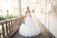 Underbar brud med en lyxig vit klänning som poserar i den gamla staden royaltyfri foto
