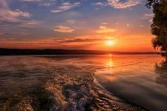 underbar liggande solnedgånghimmel med solen över den pittoreska platsen för sjö Royaltyfria Bilder