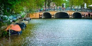 Underbar sikt av Amsterdam kanaler med deras broar och cyklar, Royaltyfria Foton