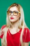 Underbar stående av den gulliga smarta flickan i glasögon och röd överkant Studio som är kort av härlig blondin på grön bakgrund Royaltyfri Bild