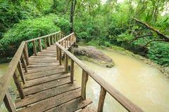 Underbar träbro över en vattenfall, Thailand Arkivfoto