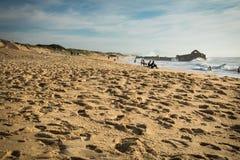 Underbara sandiga dyn och seascape med blockhus i baksidan i solig blå himmel, folk som tycker om siktssammanträde på den sandiga Arkivfoton