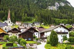 Underbara sikter av de alpina kojorna och berget som täckas med skogen Fotografering för Bildbyråer