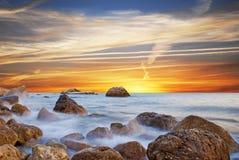 Underbart landskap med solnedgång på stranden på kusten in Royaltyfri Bild