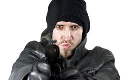 Undercover agent firing gun in the camera. Portrait of an undercover agent or delinquent dressed in black leather and balaclava hat firing handgun in the camera Stock Photo