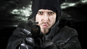 Undercover agent firing gun in the camera. Portrait of an undercover agent or delinquent dressed in black leather and balaclava hat firing handgun in the camera stock image