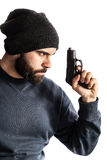 Undercover. A bearded criminal or an undercover cop with a pistol and wearing a beanie hat isolated over white Stock Photography