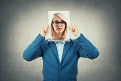 Undercover. Businessman use a woman portrait as undercover, hiding his face behind photo sheet, like a fake mask. Private life, split personality and unreal royalty free stock images