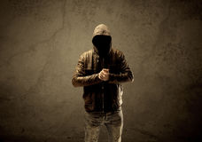 Undercover hooded stranger in the dark. A suspicious faceless mature male in dark urban environment and light in front of a concrete empty wall background Stock Images