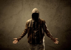 Undercover hooded stranger in the dark. A suspicious faceless mature male in dark urban environment and light in front of a concrete empty wall background Royalty Free Stock Photos