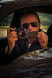 Undercover man hidden in car take photo. Undercover man detective hidden in car secretly take photo Royalty Free Stock Photography