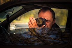 Undercover man hidden in car take photo Royalty Free Stock Photos