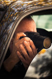 Undercover man hidden in car take photo Stock Photography