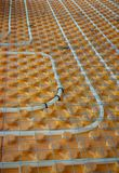 Underfloor heating. Orange posed Underfloor heating tube in a construction site Stock Images