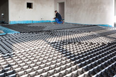 Underfloor heating and cooling. Man work on building site