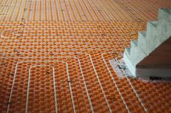 Underfloor heating with stairs. Orange Underfloor heating tube in a construction site with stairs Royalty Free Stock Photography