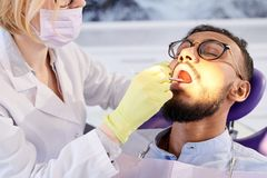 Undergoing Dental Filling. Bearded young patient undergoing dental filling while sitting on chair with opened mouth, highly professional stomatologist focused on stock images