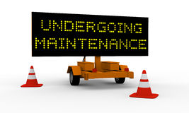 Undergoing maintenance. Black signboard on the top of a roadworks cart saying Undergoing maintenance Stock Photos