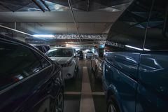 Underground car parking garage with many automobiles in modern mall or shopping center inside stock photos