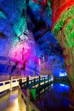Around China - The impressive Fengshuidong caver with water pool and stone bridge. In the underground cave system known as Fengshuidong the icolored lights make stock image
