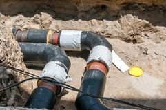 Underground district heating pipeline reparation and reconstruction on the street in the city old ones replacement with new pipes.  stock photo