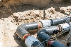 Underground district heating pipeline reparation and reconstruction on the street in the city old ones replacement with new pipes.  stock photos