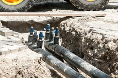 Underground district heating pipeline reparation and reconstruction on the street in the city old ones replacement with new pipes.  stock images