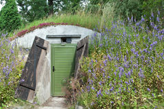 Underground dwelling under a blooming hill. Door to an underground dwelling built under a hill Stock Photography