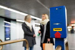 Underground entrance with turnstile. Two unrecognizable women. Royalty Free Stock Photography