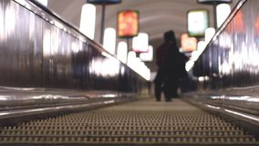 Underground escalators at rush hour. Blurred background with bokeh lights. 3840x2160, 4k. Underground escalators at rush hour stock footage