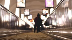 Underground escalators at rush hour. Blurred background with bokeh lights. 3840x2160. Underground escalators at rush hour stock video footage